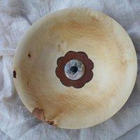 Kastanienschale mit versteinertem Holzring und eingelegter Blume.