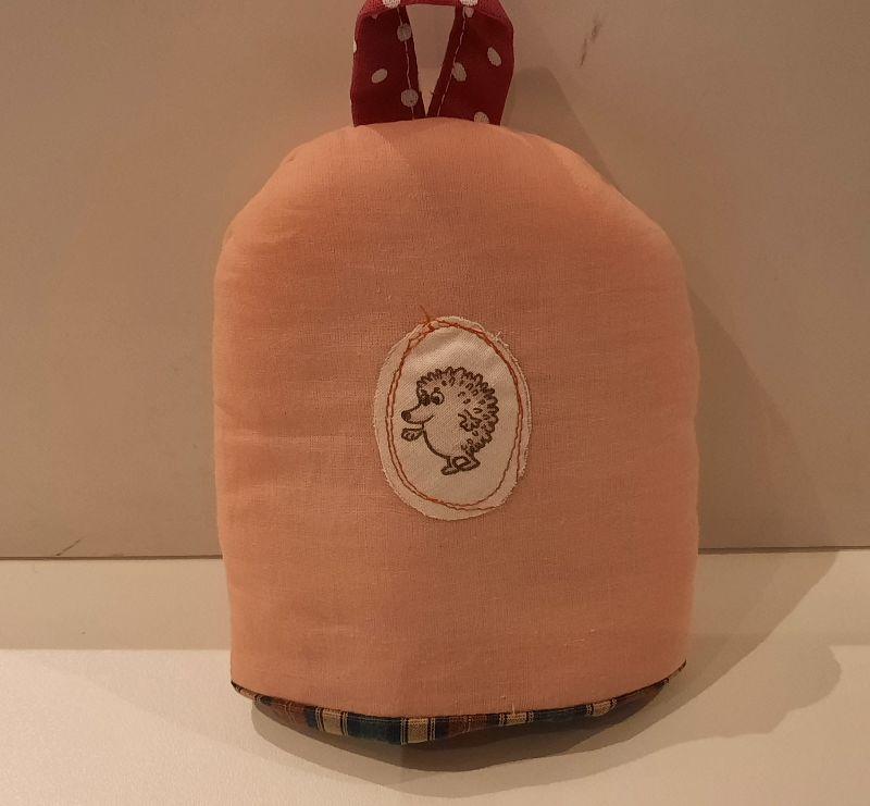 - Eierwärmer mit appliziertem Igel auf aprico-farbigem Baumwoll-Stoff mit kleinem Henkel und einem wattierten in Karo gehaltenen Innenstoff  - Eierwärmer mit appliziertem Igel auf aprico-farbigem Baumwoll-Stoff mit kleinem Henkel und einem wattierten in Karo gehaltenen Innenstoff