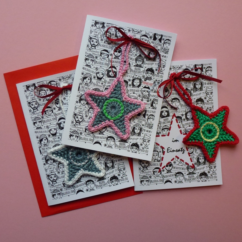 Kleinesbild - Weihnachtskarte mit Grüßen in vielen Sprachen und Schriften und abnehmbaren handgehäkeltem Stern