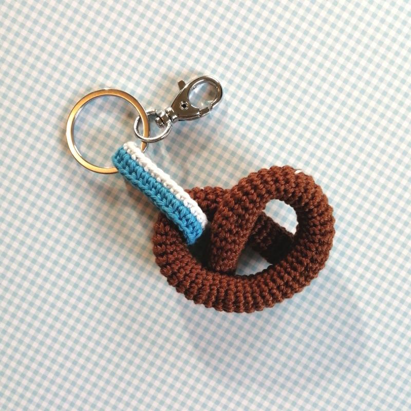 Kleinesbild - Schlüsselanhänger Taschenbaumler Brezel mit blau-weißem Band aus Baumwolle gehäkelt mit Karabiner