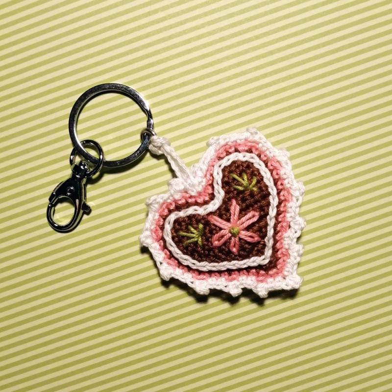 Kleinesbild - Schlüsselanhänger Taschenbaumler Lebkuchenherz mit Blümchen und viel Zuckerguss mit Buchstaben personalisierbar aus Baumwolle gehäkelt mit Karabiner