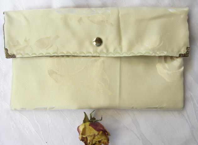 Kleinesbild - Handgefertigte Clutch aus cremefarbigem Stoff mit schimmernden Blüten kaufen