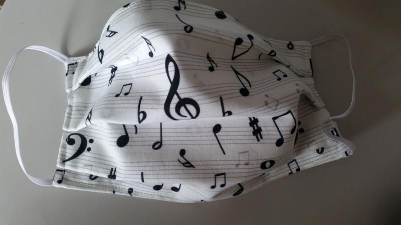 - weiße Gesichtsmaske mit vielen Noten und anderen Musikzeichen, doppellagig aus Baumwolle  - weiße Gesichtsmaske mit vielen Noten und anderen Musikzeichen, doppellagig aus Baumwolle