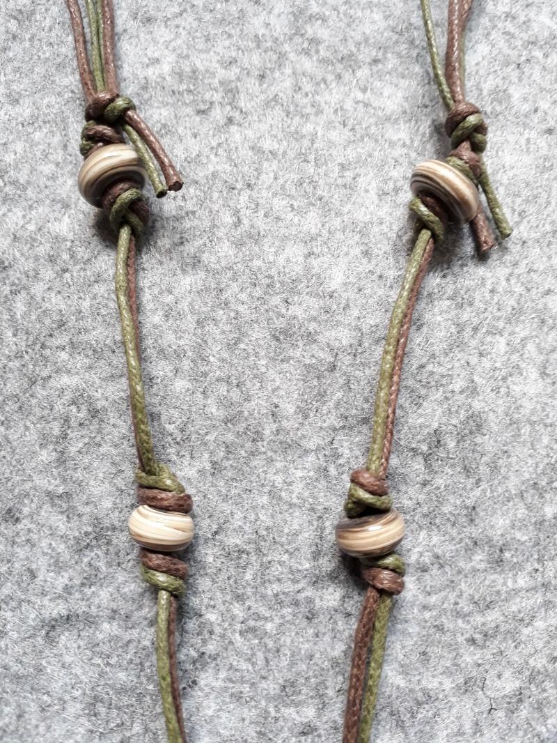 Kleinesbild - Eine schöne Kette in Braun-olivtönen mit gedrehten Perlen und einem Baumanhänger aus Metall