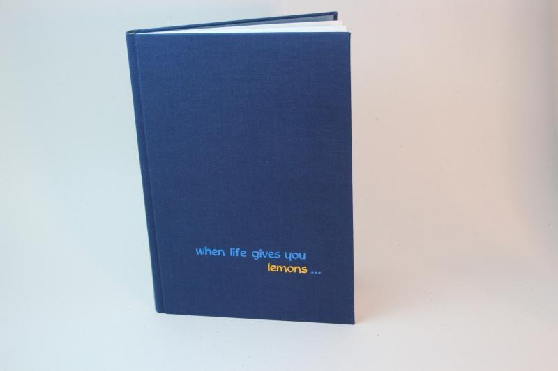 """Kleinesbild - handeingebundenes Schreibbuch in blauem Mattleinen-Einband mit zweifarbiger Titelprägung """"When life gives you lemon..."""""""