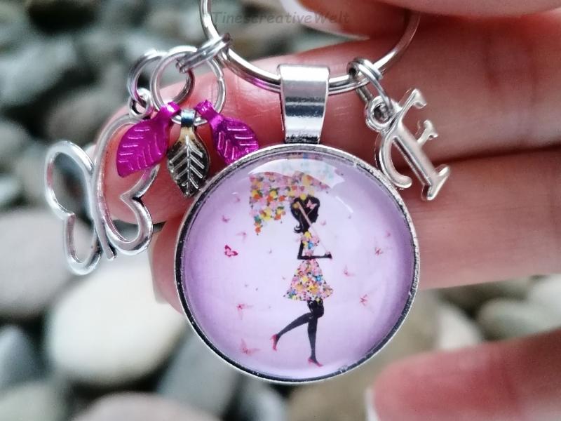 Kleinesbild - Personalisierbarer Schlüsselanhänger, Glascabochon, Frau mit Regenschirm aus Blumen und Schmetterling, Fee, Geschenk für Frauen