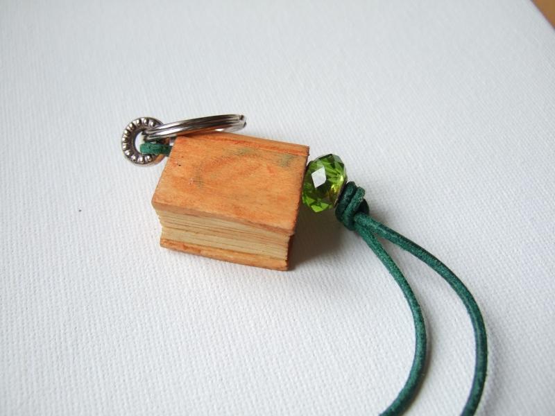 Kleinesbild - Schlüsselanhänger in Buchform aus Holz in orange mit Perle und grünem Lederband