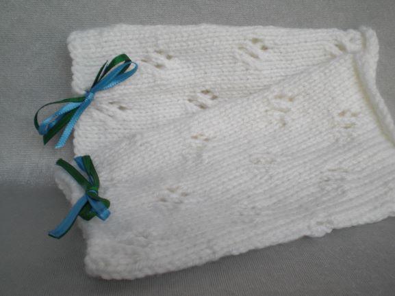 Kleinesbild - handgestrickte Pulswärmer in wollweiß mit Lochmuster und kleiner Satinschleife in grün und blau kaufen