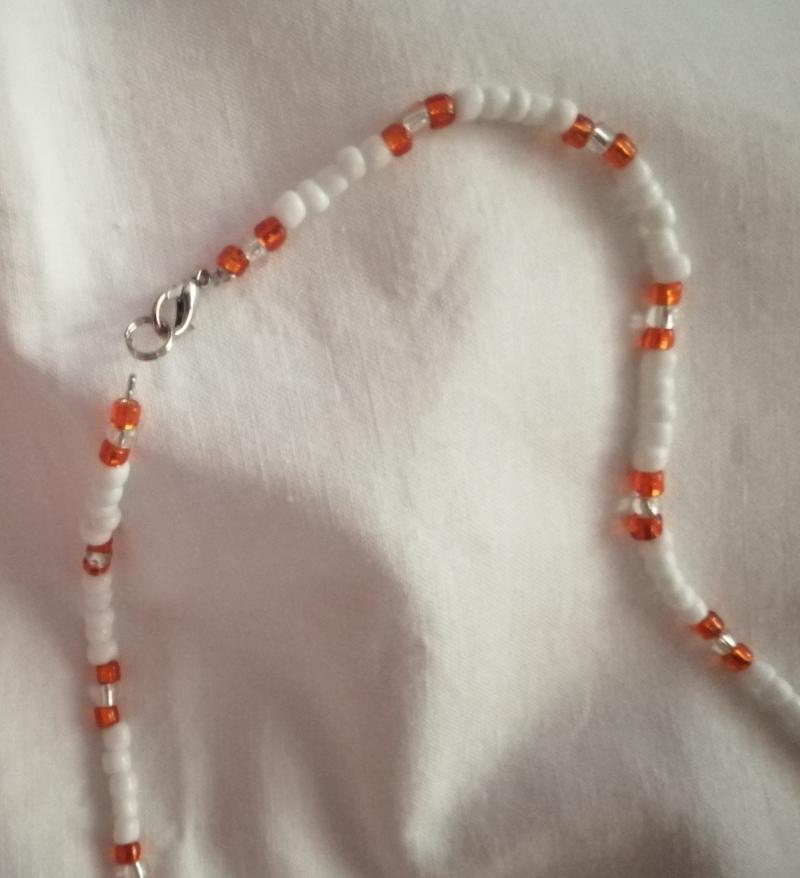 Kleinesbild - Hübsche zarte Halskette in Weiß und Orange, mit einer Kaurimuschel als Highlight