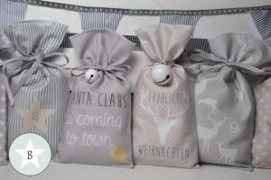 Adventskalender zum Befüllen aus Stoff in zarten Pastelltönen, jedes Säckchen mit bedrucktem Motiv und Zahl