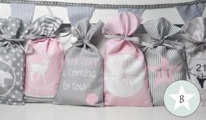 Adventskalender zum Befüllen aus Stoff in zarten rosa Pastelltönen, jedes Säckchen mit bedrucktem Motiv und Zahl