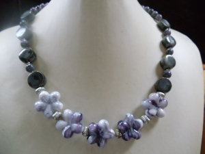 Tolle süß-lila farbene Keramik Blumen vereint mit gräulichen, runden Perlen - Handarbeit kaufen