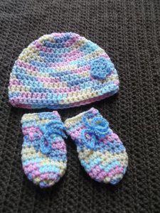 Gehäkeltes Babyset Mütze und Fäustlinge für Neugeborene in pastellfarben mit Blümchen