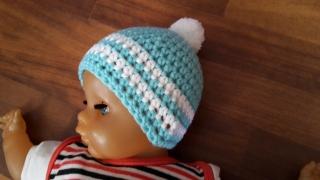 Gehäkelte Babymütze für den Winter in türkis mit weißen Streifen und Bommel