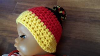 Gehäkelte Babymütze für den Winter in schwarz rot gelb mit Bommel