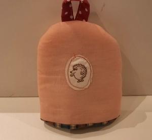 Eierwärmer mit appliziertem Igel auf aprico-farbigem Baumwoll-Stoff mit kleinem Henkel und einem wattierten in Karo gehaltenen Innenstoff  - Handarbeit kaufen