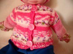 Jacke und Mütze für Puppengröße 50. Durch verschieden eingefärbte Wolle entstand dieses schöne Muster. Die meisten Farben sind rosa und dunkel rosa. Dann weiß, im Muster sind noch