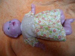 Puppenkleid für Puppengröße 35 – 45 cm. Das  Kleidchen ist im Vorder- und Rückenteil aus hellbraunen BW-Stoff mit weißen Schäfchen bedruckt.