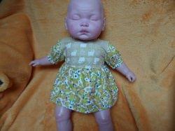 Puppenkleid für Puppengröße 35 – 42 cm. Die Ärmel und das Röckchen sind aus Baumwollstoff mit kleinen Blümchen