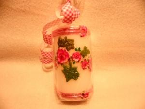Eine weiße, runde Kerze in rosa Tönen mit Blüten und grünen Blättern gestaltet.