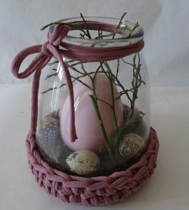 Ein Keramikei im Glas und mit Zubehör dekoriert