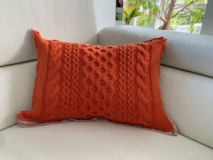 Handgestricktes orangenes Kissen mit Stoffrückseite im Landhausstil