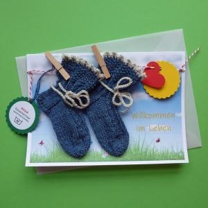 Grußkarte Willkommen im Leben Geburt mit handgestickten Baby-Söckchen mit Zopfmuster für Neugeborene an einer Wäscheleine