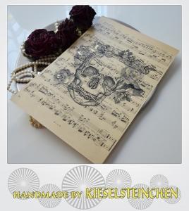 Schmuckblatt aus alten Notenpapier mit neuem Druck eines Totenkopf