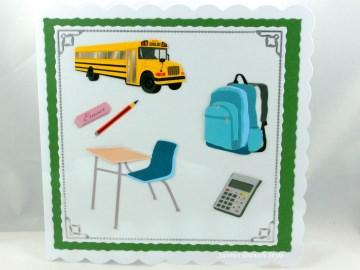 Glückwunschkarte für den Schulanfang mit Schulbus, Tisch und Stuhl samt Schultasche, ca. 15 x 15 cm