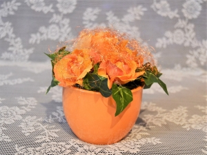 Gesteck in orange im Keramiktopf mit goldenem Feenhaar überzogen.