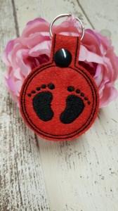 Schlüsselanhänger aus rotem Stickfilz und schwarzen Baby Füsschen