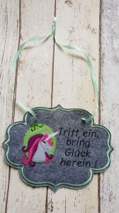gesticktes Türschild aus grauem Stickfilz mit Einhornapplikation und Spruch, an einem grünen Satinband