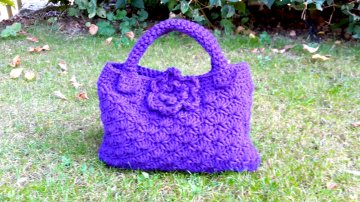 Häkeltasche in lila im Muschelmuster mit Verschluss und Blume