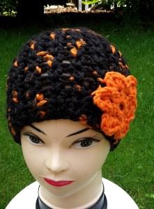 Häkelmütze in dunkelbraun mit Blume in orange, Kopfumfang ca. 51-55 cm