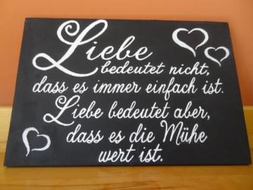 Holzschild mit Tafelkreide bemalt mit dem Spruch Liebe ist nicht einfach