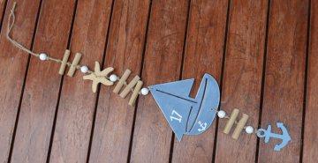 Maritime Kette mit Segelschiff und  gesammelten Teibholzstücken