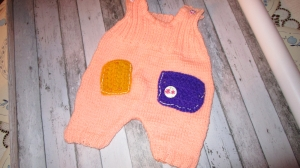 gestrickte korallfarbene Baby-Latzhose Gr. 62