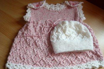 Niedliches rosa handgestricktes Babykleidchen mit weißer Mütze