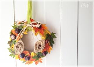 Herbstlicher Türkranz aus bunten Blättern und Kastanien