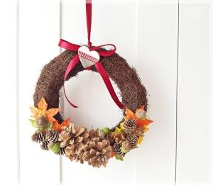 Rebenkranz als herbstlicher Türkranz aus bunten Blättern und Zapfen mit rotem Schleifenband