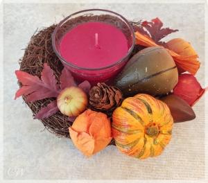 Rebenkranz als herbstlicher Tischkranz aus bunten Blättern und Kürbissen