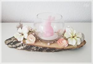 Osterdeko auf Baumscheibe als Tischschmuck zu Ostern und Frühling mit Glasvase und Kerze als Osterhase rosa
