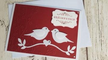 Hochzeitskarte mit zwei flirtenden Tauben und geprägtem Hintergrund in chili-rot