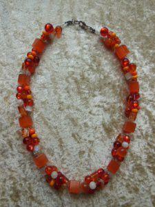 Kette aus orangen und weißen Cat-Eye Würfeln und Perlen