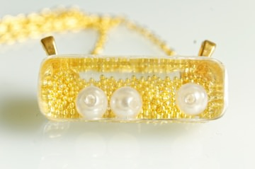 Handgemachte goldfarbene Kette mit eingegossenen Perlen in viereckigem Anhänger aus Resin (Harz)