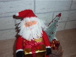 gehäkelter Weihnachtsmann mit Geschenken  auf einer Holzbank
