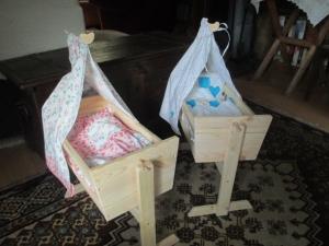Handgefertigte Puppenwiege mit Bettzeug aus naturbelassenem Holz.