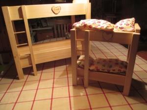 Handgefertigtes Puppenhochbettchen mit Bettzeug aus naturbelassenem Holz.