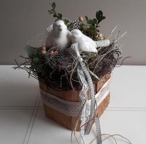 Tischdeko Frühling dekorativer alter Holzbalken mit Vogelnest und Naturmaterialien