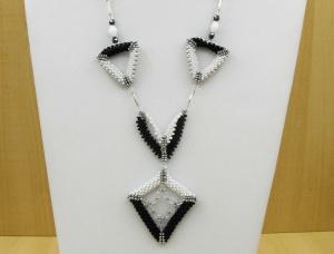 geometrische Kette aus Rocailles mit dreieckigen und drachenförmigen Elementen; schwarz-weiß-silber - Handarbeit kaufen